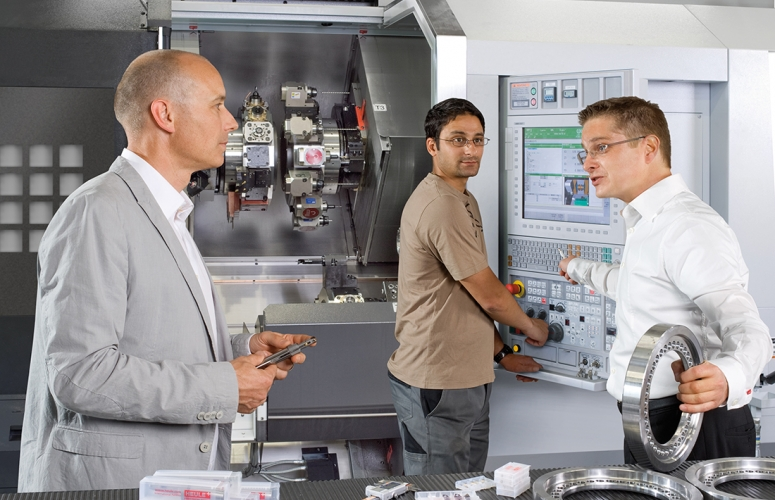 Manufacturing engineers discussing the best deburring tools for aluminum next to a CNC machine