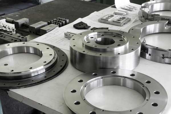 picture of metal parts with holes that have been machined and deburred on CNC machines in a machine shop